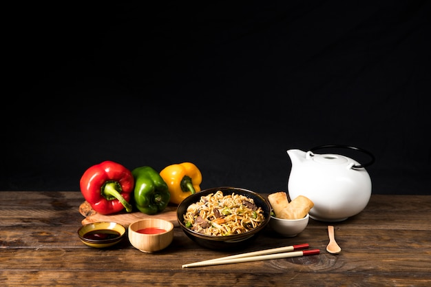 Una ciotola di deliziosi teriyaki di manzo con noodles di udon; salsa di soia; ruolo di peperone dolce e primavera con le bacchette e cucchiaio sul tavolo di legno Foto Gratuite