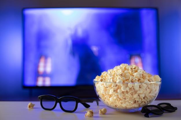 Una ciotola di vetro di popcorn, occhiali 3d e telecomando. Foto Premium