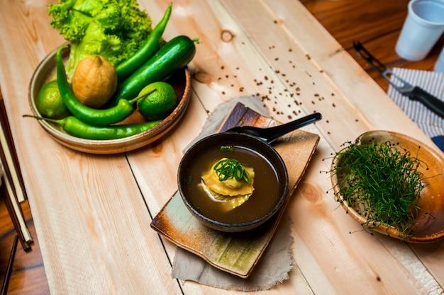 Una ciotola di zuppa di gnocchi giapponese, piatto di verdure e frutta e ciotola di erbe Foto Gratuite