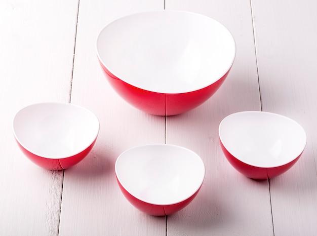 Una ciotola e tazze di insalata rosse vuote su una tavola di legno bianca Foto Premium