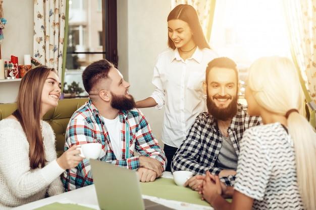 Una compagnia di amici felici che si incontrano in un ristorante Foto Premium