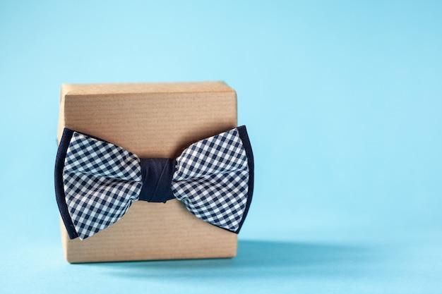 Una confezione regalo avvolta in carta artigianale e legata con il papillon su sfondo blu. concetto festa del papà. Foto Premium