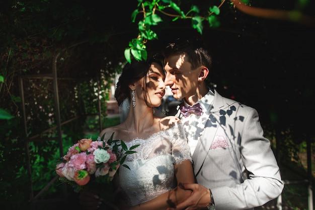 Una coppia amorosa di sposi si abbracciano dolcemente all'ombra degli alberi Foto Premium