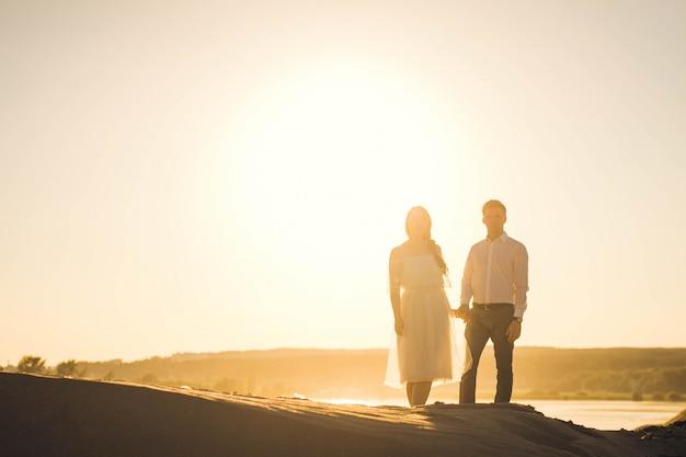Una coppia di amanti si tiene per mano. silhouette di vlaenne contro il sole. coppia fuori fuoco. Foto Premium