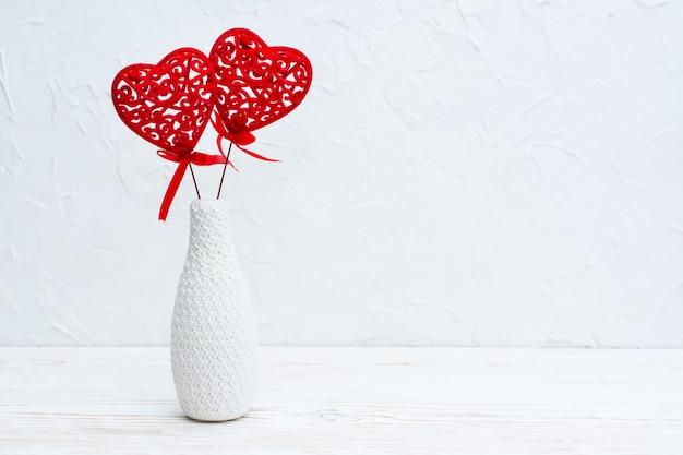 Una coppia di cuori rossi ricci in un vaso bianco decorato a maglia sul tavolo. copia spase Foto Premium