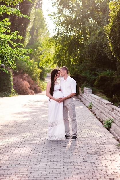 Una coppia incinta amorosa abbraccia in un parco estivo e sorride Foto Premium