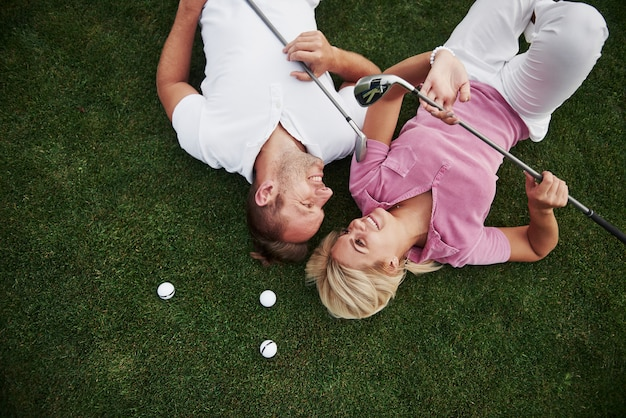 Una coppia, marito e moglie si trovano sul campo da golf e si rilassano dopo la partita Foto Premium