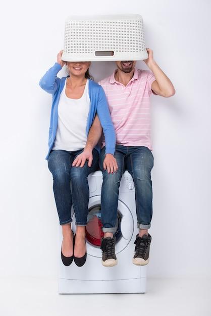Una coppia si siede su una lavatrice e si copre il viso. Foto Premium
