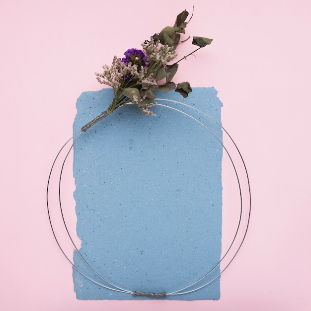 Una cornice decorativa vuota realizzata con cavo metallico e bouquet di fiori su carta su sfondo rosa Foto Gratuite