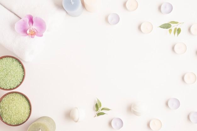 Una cornice vuota circondata da una ciotola di sale alle erbe e candele Foto Gratuite