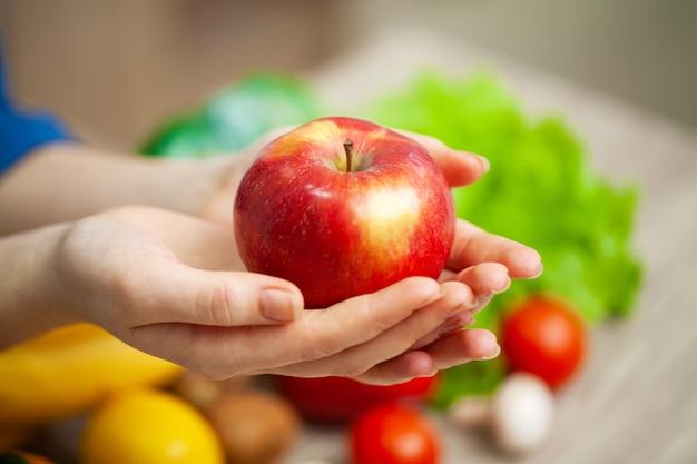 Una donna a un tavolo in possesso di una mela Foto Premium