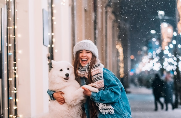 Una donna abbraccia il suo cane in una strada di notte. Foto Gratuite
