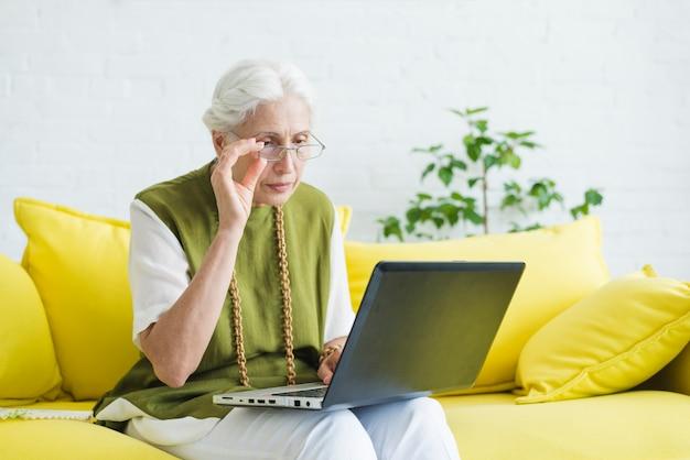 Una donna anziana che si siede sul sofà giallo che esamina computer portatile Foto Gratuite
