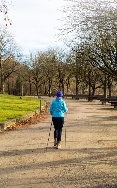Una donna anziana pratica il nordic walking. Foto Premium