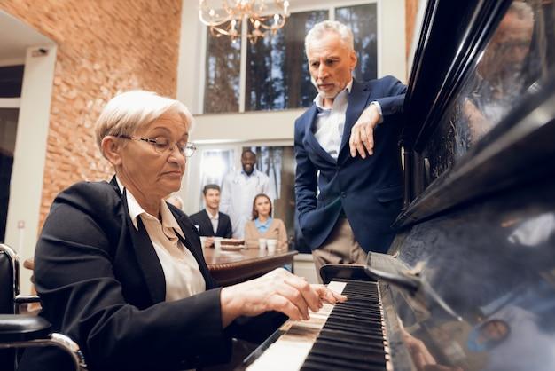 Una donna anziana suona il piano in una casa di riposo Foto Premium