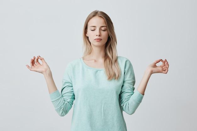 Una donna bionda pacifica e riposante si sente rilassata, si trova nella posa del loto, cerca di concentrarsi o di concentrarsi, chiude gli occhi, gode del silenzio, cerca di trovare l'equilibrio. atmosfera calma e meditazione Foto Gratuite