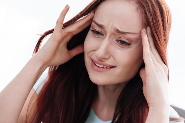 Una donna bruna ha un mal di testa in backround bianco Foto Premium