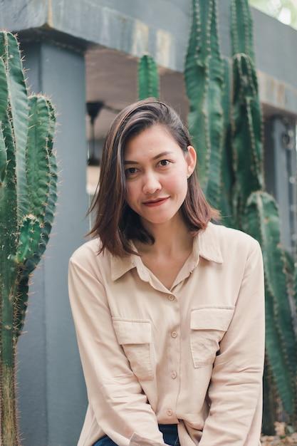 Una donna che indossa una camicia marrone seduto con un cactus Foto Premium