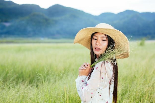 Una donna che tiene in mano un'erba su un bellissimo campo in erba con una montagna. Foto Gratuite