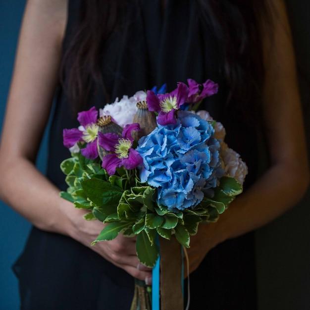 Una donna con un mazzo di lillà e rose viola nella mano Foto Gratuite