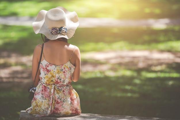 Una donna con una macchina fotografica che si siede e che affronta indietro su uno sfondo naturale Foto Gratuite