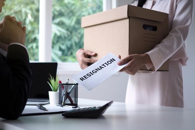 Una donna d'affari in possesso di una scatola di cartone marrone e invia una lettera di dimissioni alla direzione. spostamento di posti di lavoro e posti vacanti Foto Premium