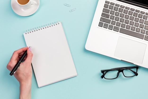Una donna d'affari scrivendo sul blocco note a spirale sulla scrivania Foto Gratuite