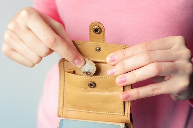 Una donna in un maglione mette una moneta in euro in una borsa marrone Foto Premium