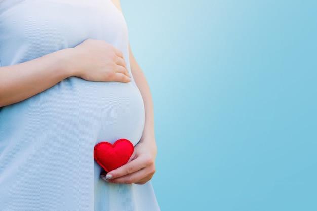 Una donna incinta in un vestito blu tiene tra le mani un cuore rosso sul blu. concetto di gravidanza Foto Premium