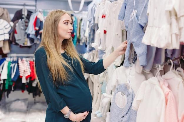 Una donna incinta sceglie vestiti per bambini nel negozio. Foto Premium