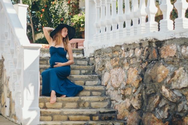 Una donna incinta si siede sui gradini di pietra di un edificio storico. turista in gita. ragazza in vacanza Foto Premium