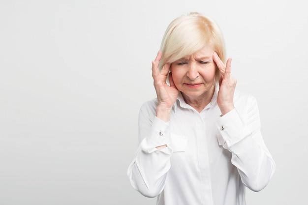 Una donna malata e anziana si sta toccando la testa mostrando di avere mal di testa. probabilmente si ammalerà. avvicinamento. Foto Premium