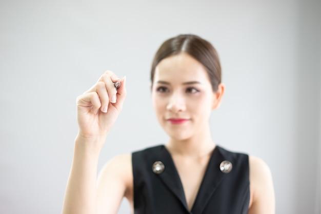 Una donna sta scrivendo sullo schermo. sta presentando la nuova idea. con sfondo sfocato Foto Premium