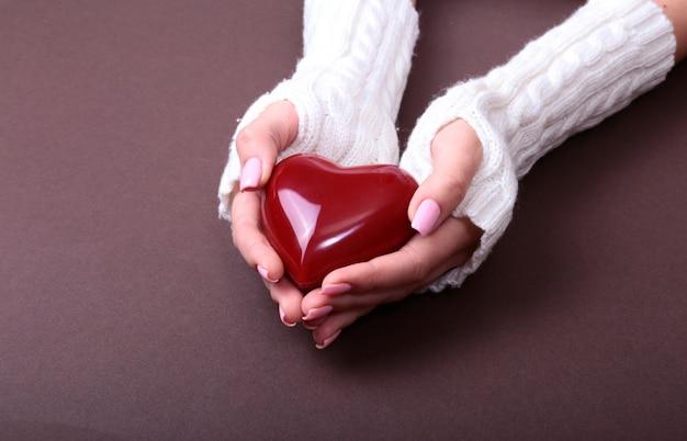 Una donna tiene in mano un cuore rosso Foto Premium