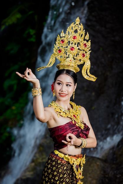 Una donna vestita con un abito thailandese antico presso la cascata. Foto Gratuite