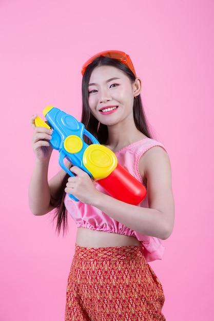 Una donna vestita in abiti tradizionali tailandesi tradizionali tenendo una pistola ad acqua su uno sfondo rosa. Foto Gratuite