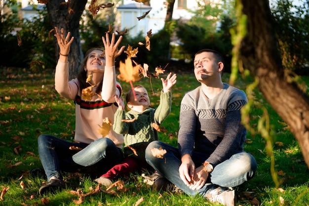 Una famiglia di tre persone gode del parco in autunno divertendosi con il sorriso Foto Premium
