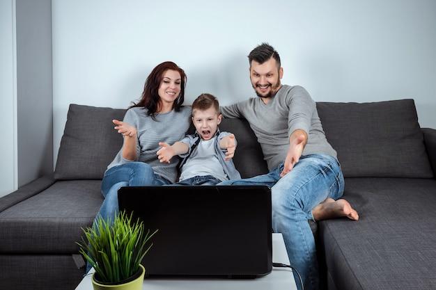 Una famiglia felice con sorrisi guardando qualcosa in un computer portatile Foto Premium