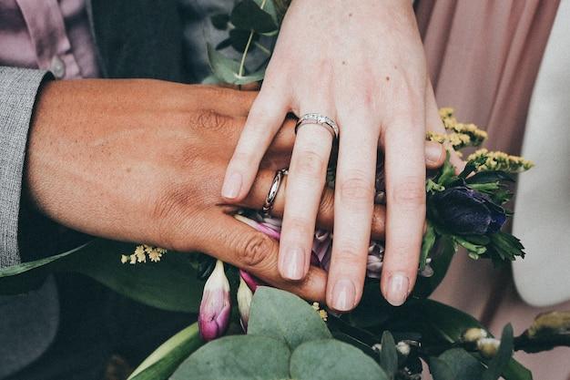 Una femmina caucasica e un maschio afroamericano indossano anelli e tengono i fiori concetto di diversità Foto Gratuite