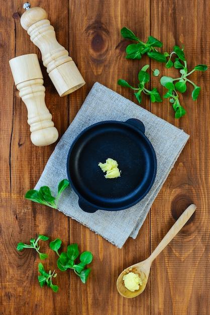 Una fetta di burro ghi in una padella di ghisa con verdure e spezie. Foto Premium