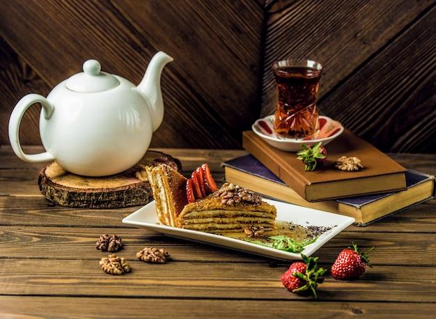 Una fetta di torta al miele, medovik con un bicchiere di tè Foto Gratuite