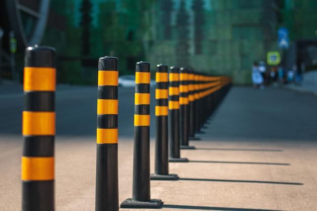 Una fila di barriere gialle sulla strada, che separa le linee di traffico e la zona pedonale. Foto Premium