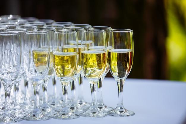 Una fila di bicchieri pieni di champagne sono allineati pronti per essere serviti Foto Premium