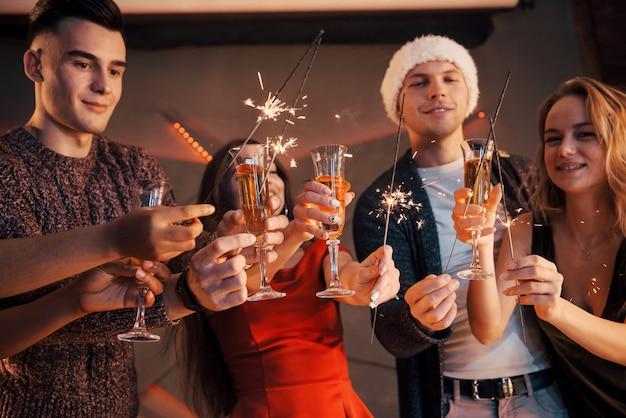 Una foto con un gruppo di amici che si divertono con pupazzi di neve e champagne. felice anno nuovo. avvicinamento. Foto Premium
