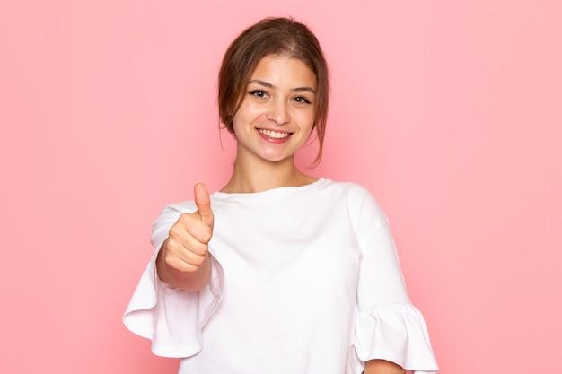 Una giovane bella femmina di vista frontale in camicia bianca che posa con l'espressione felice Foto Gratuite