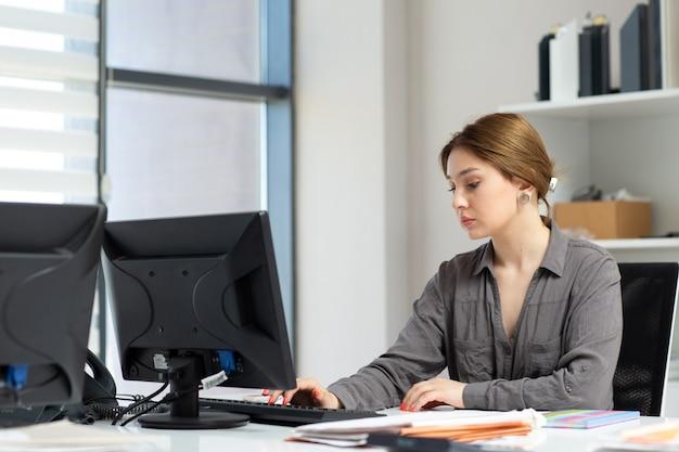 Una giovane bella signora di vista frontale in camicia grigia che lavora con i documenti facendo uso del suo pc che si siede dentro il suo ufficio durante l'attività di lavoro di costruzione di giorno Foto Gratuite