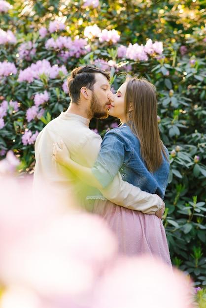 Una giovane coppia in amore ragazzo e ragazza bacio sullo sfondo di un rododendro in fiore. primo appuntamento. san valentino Foto Premium