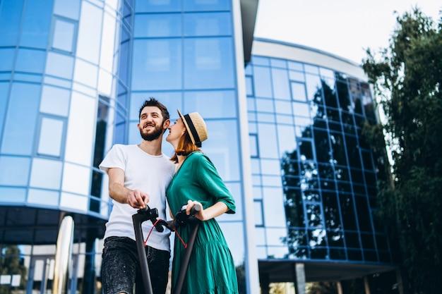 Una giovane coppia romantica con scooter elettrici in una data, camminando in città. Foto Premium