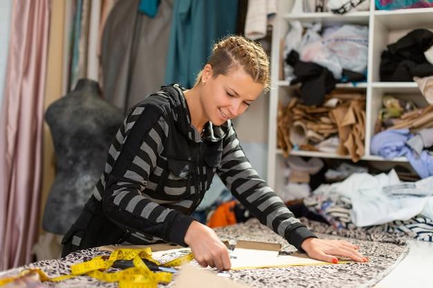Una giovane designer di abiti. misure per centimetro di taglio sul tessuto per realizzare abiti Foto Premium
