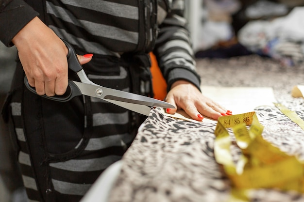 Una giovane designer di abiti, taglia il tessuto su disegno per creare abiti nel suo laboratorio Foto Premium